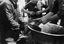 deux hommes font résonner un chaudron en faisant grincer des joncs mouillés ; 1er mouvement, François Le Brun tire sur les joncs ; on aperçoit l'eau dans le fond du chaudron ; 25 juillet à 14h ; Surzur ; pré de Mme Jégo ; [photo originale 57]